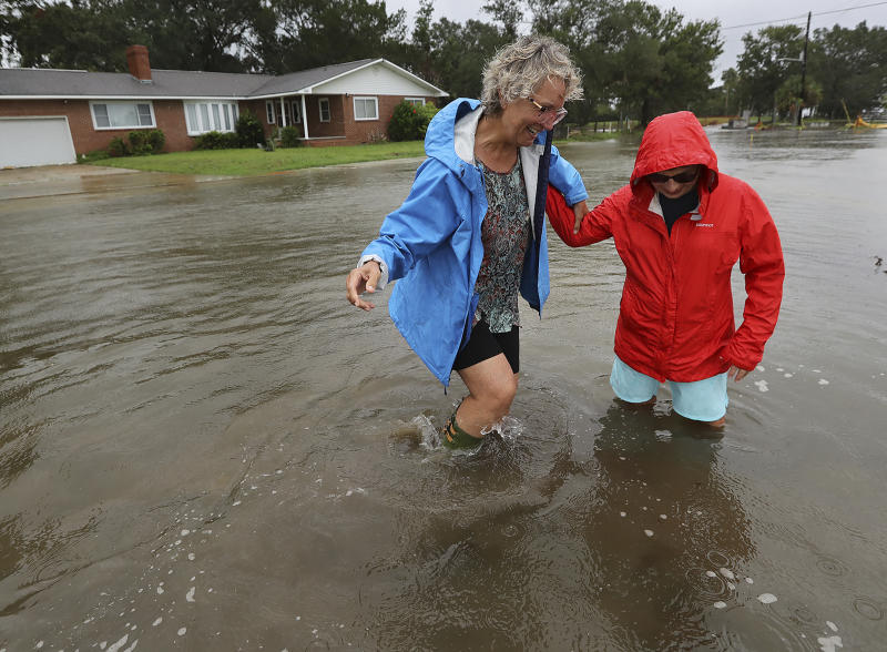 St. Mary's: Anne Herring (right) helps support her friend Jen Fabrick (left) as they walk through flood waters near their homes on St. Mary's Street while Hurricane Dorian passes by on Wednesday, Sept. 4, 2019, at St. Mary's. (Photo: Curtis Compton/Atlanta Journal-Constitution via AP)