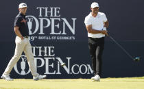 United States' Brooks Koepka, right, watches his ball after teeing off from the 1st as Canada's Mackenzie Hughes walks to the tee box during the third round of the British Open Golf Championship at Royal St George's golf course Sandwich, England, Saturday, July 17, 2021. (AP Photo/Peter Morrison)