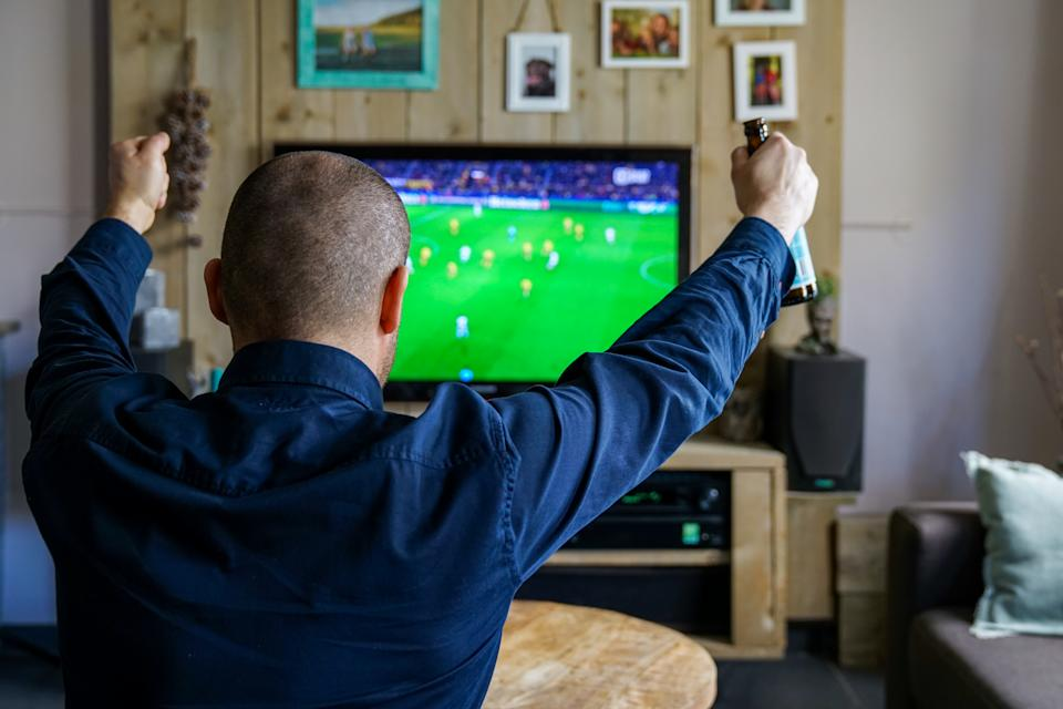 Rear View Of Man Enjoying Soccer Match On Television Set In Living Room At Home