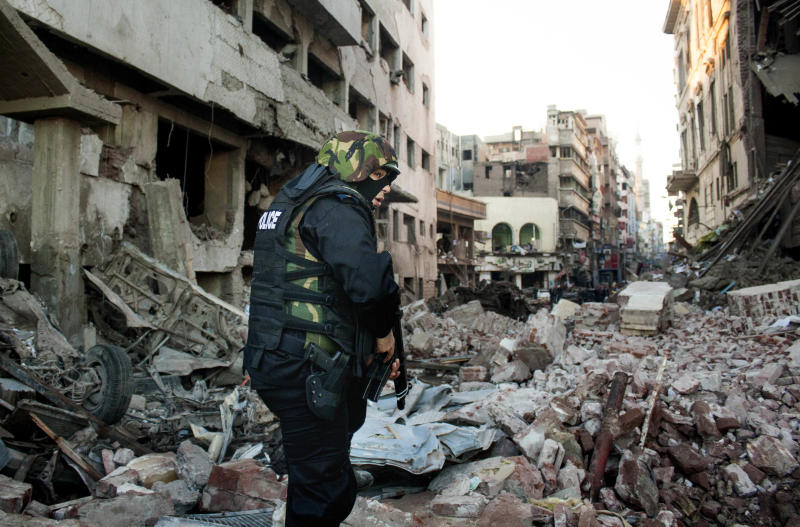 "An Egyptian policeman stands guard at the scene of an explosion at a police headquarters building that killed at least a dozen people, wounded more than 100, and left scores buried under the rubble, in the Nile Delta city of Mansoura, 110 kilometers (70 miles) north of Cairo, Egypt, Tuesday, Dec. 24, 2013. The country's interim government accused the Muslim Brotherhood of orchestrating the attack, branding it a ""terrorist organization."" No one immediately claimed responsibility for the bombing, which came a day after an al-Qaida-inspired group called on police and army personnel to desert or face death at the hands of its fighters. (AP Photo/Ahmed Ashraf)"