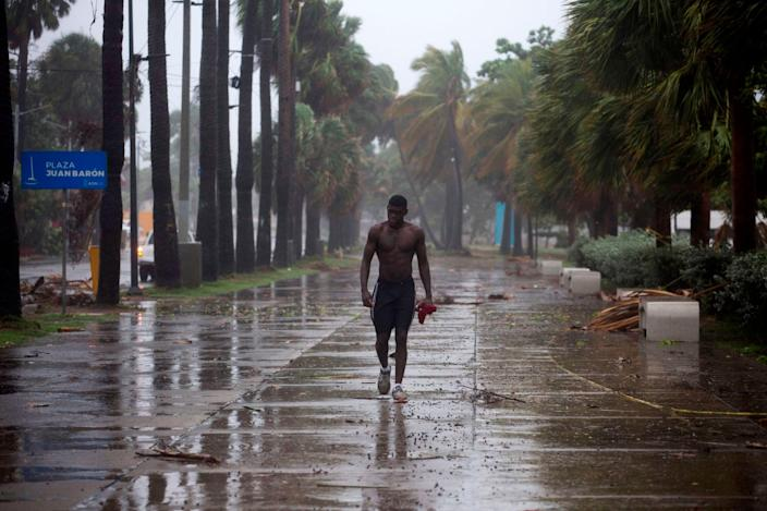 A man walks under pouring rain during Storm Isaias, then a tropical storm, in Santo Domingo, Dominican Republic, on July 30, 2020.