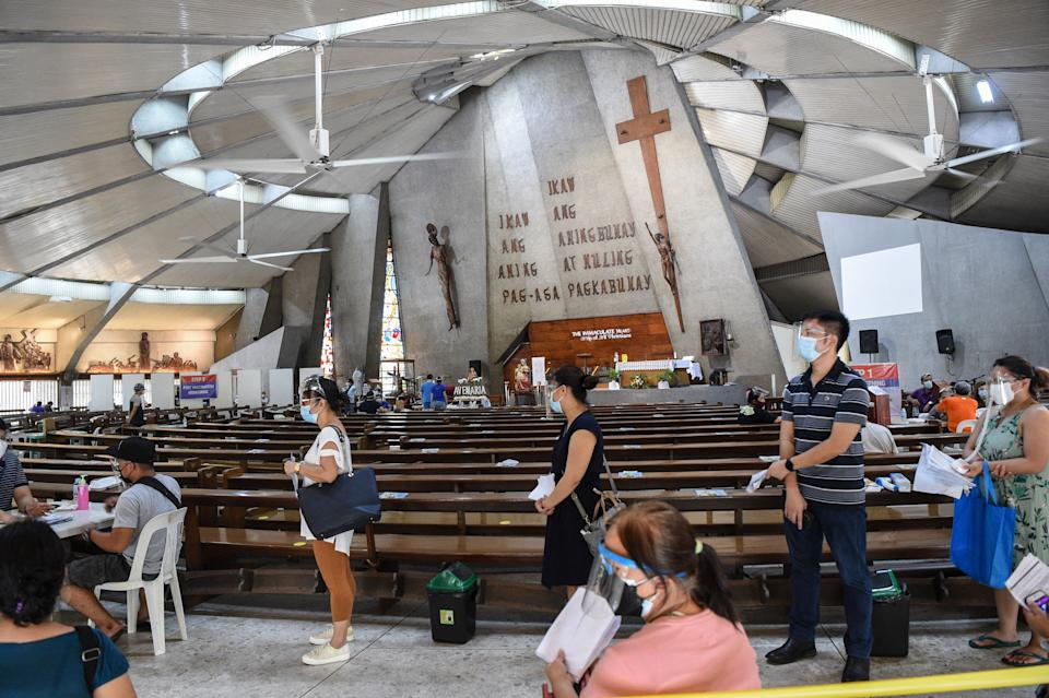 Residents wearing face masks and shields queue up to receive a dose of the AstraZeneca/Oxford Covid-19 coronavirus vaccine inside a Catholic church turned into a vaccination center in Manila on May 21, 2021. (Photo by Ted ALJIBE / AFP) (Photo by TED ALJIBE/AFP via Getty Images)