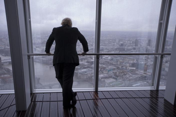 "FILE - In this Friday, Feb. 1, 2013 file photo then London mayor Boris Johnson poses for photographers by looking out at the sights after officially opening ""The View"" viewing platform at the Shard skyscraper in London. (AP Photo/Matt Dunham, File)"
