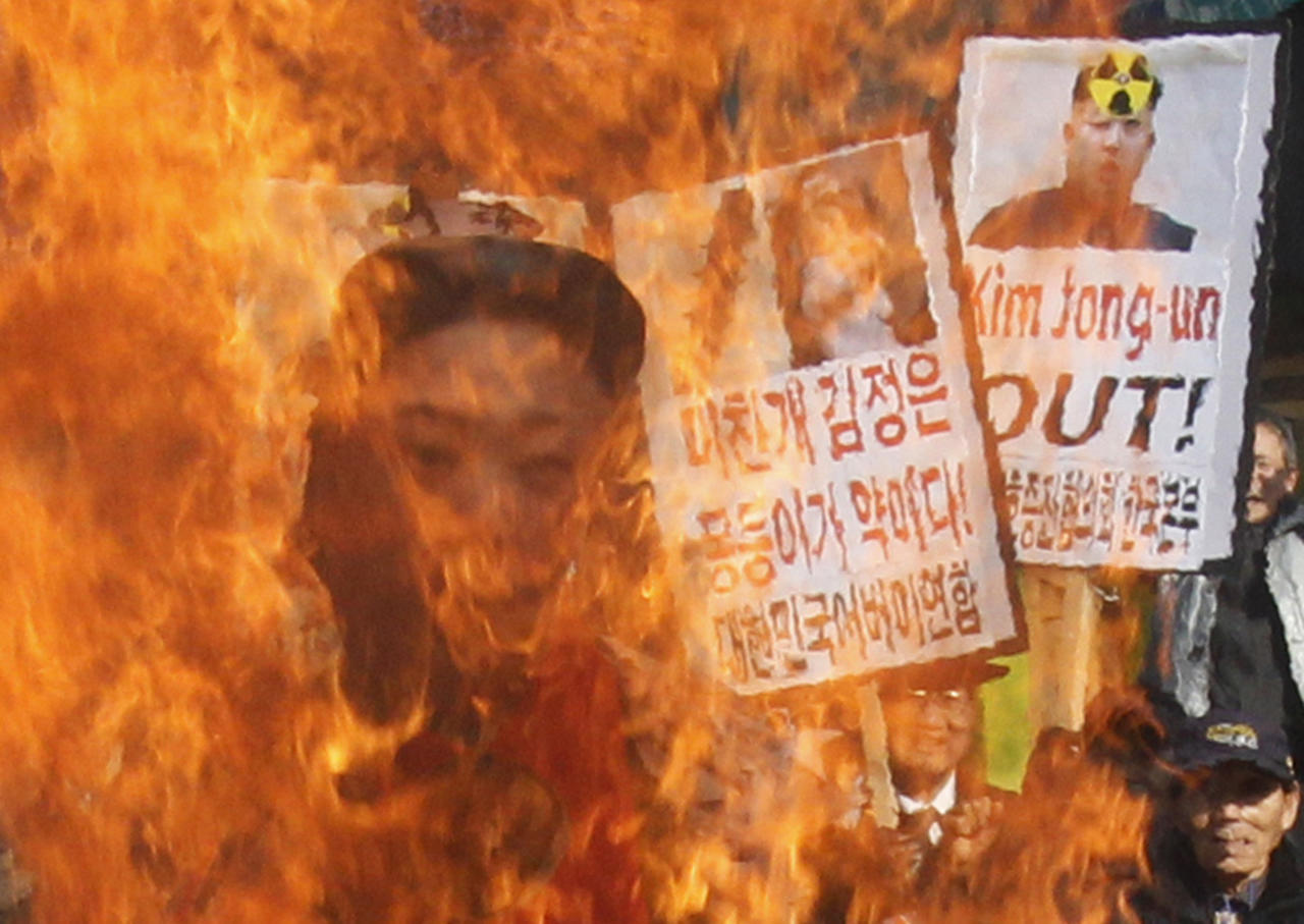 South Korean protesters burn an effigy of North Korean leader Kim Jong Un during an anti-North Korea rally denouncing the North's nuclear test in Seoul, South Korea, Wednesday, Feb. 13, 2013. A day after North Korea defied U.N. warnings with a nuclear test, Pyongyang's neighbors turned Wednesday to the business of bolstering their military preparations and sending out scientists to determine whether the detonation was as successful as the North claimed. (AP Photo/Ahn Young-joon)