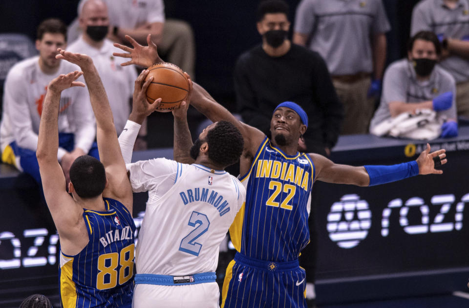 Indiana Pacers guard Caris LeVert (22) attempts to block a shot by Los Angeles Lakers center Andre Drummond (2) as teammate center Goga Bitadze (88) helps on defense during the second half of an NBA basketball game in Indianapolis, Saturday, May 15, 2021. (AP Photo/Doug McSchooler)
