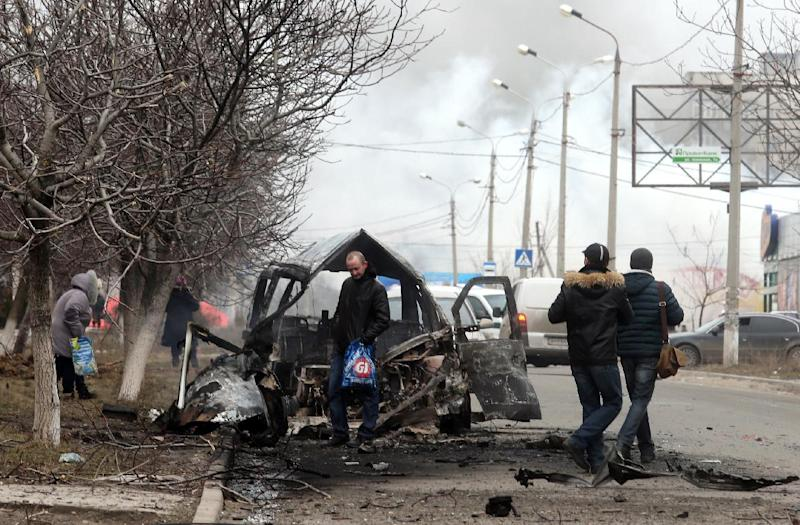 People walk past a destroyed truck after shelling in the southern Ukrainian port city of Mariupol on January 24, 2015 (AFP Photo/)