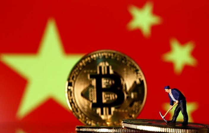 FILE PHOTO: Picture illustration of a small toy figurine and representations of the Bitcoin virtual currency displayed in front of an image of China's flag