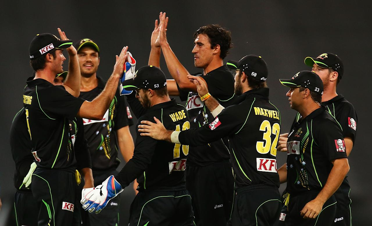 SYDNEY, AUSTRALIA - FEBRUARY 02: Mitchell Starc of Australia celebrates with team mates after getting the wicket of Luke Wright of England during game three of the International Twenty20 series between Australia and England at ANZ Stadium on February 2, 2014 in Sydney, Australia.  (Photo by Mark Nolan/Getty Images)