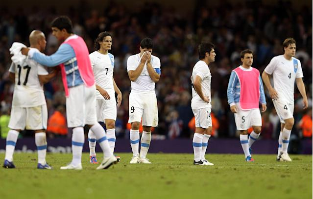 CARDIFF, WALES - AUGUST 01: Luis Suarez of Uruguay and team look down after losing during the Men's Football first round Group A match between Great Britain and Uruguay on Day 5 of the London 2012 Olympic Games at Millennium Stadium on August 1, 2012 in Cardiff, Wales. (Photo by Julian Finney/Getty Images)