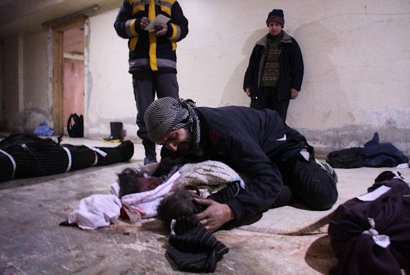 A man weeps over his child at a make-shift morgue in Douma who was killed in air strikes on the Syrian village of Mesraba in the besieged Eastern Ghouta region on the outskirts of the capital Damascus (AFP Photo/Hamza Al-Ajweh)