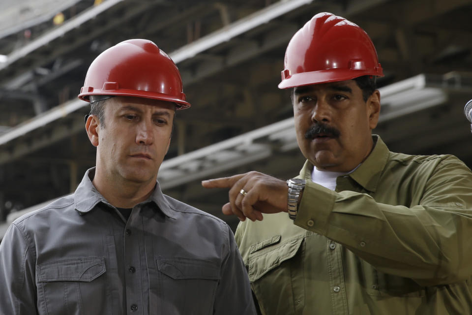 FILE - In this May 19, 2018 file photo, Venezuela's President Nicolas Maduro, right, and then Vice President Tareck El Aissami tour the construction site of La Rinconada baseball stadium on the outskirts of Caracas, Venezuela. The prosecution of El Aissami, Venezuela's Oil Minister, for violating U.S. sanctions has run into another snag after a federal judge on Monday, Nov. 2, 2020, allowed one of his co-defendants to withdraw a guilty plea over allegations U.S. attorneys withheld evidence in the case. (AP Photo/Ricardo Mazalan, File)