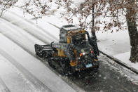 A snow clearing machine cleans a road during heavy snow, Saturday, Dec. 5, 2020, in Marlborough, Mass. The northeastern United States is seeing the first big snowstorm of the season. (AP Photo/Bill Sikes)