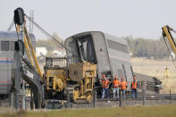 Workers walk Sunday, Sept. 26, 2021, next to an Amtrak train that derailed Saturday just west of Joplin, Mont. The westbound Empire Builder was en route to Seattle from Chicago, with two locomotives and 10 cars. (AP Photo/Ted S. Warren)