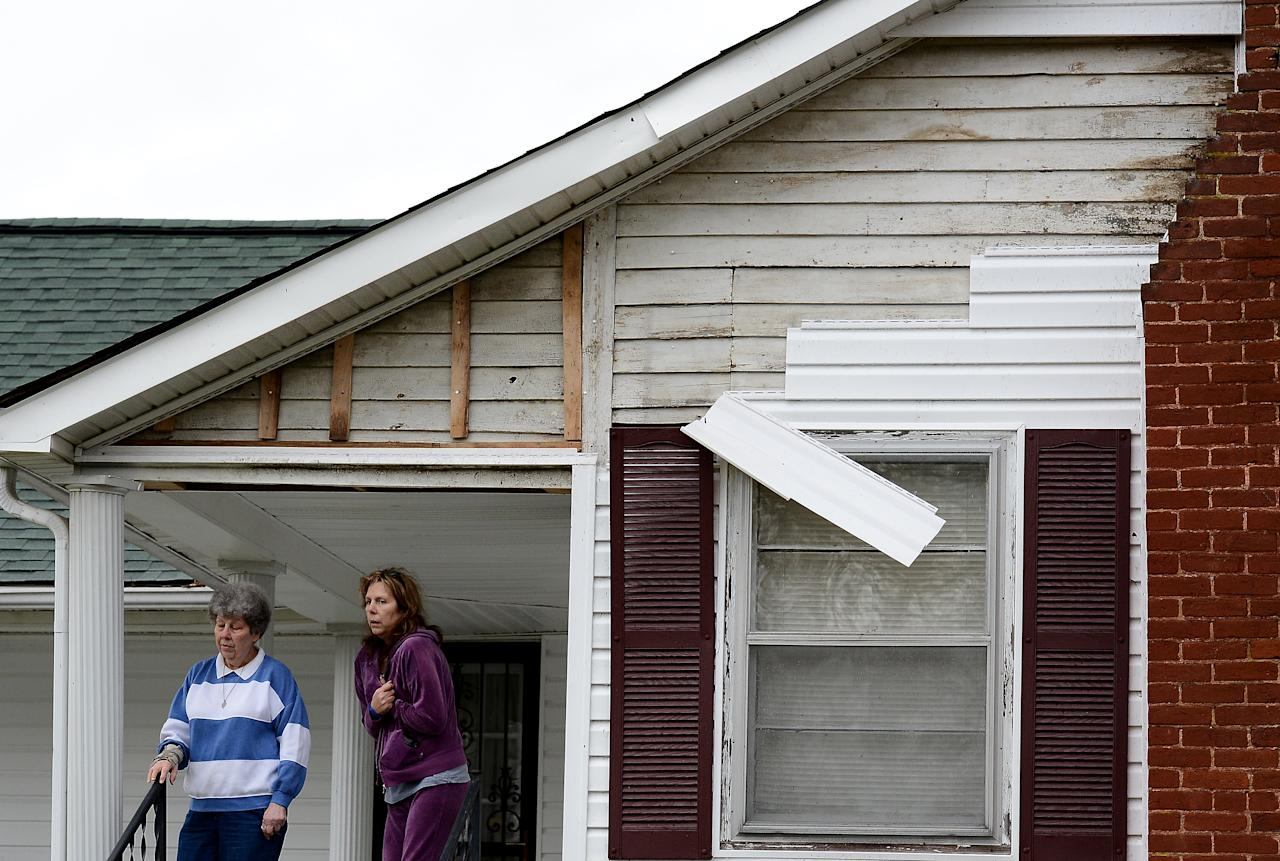 Jean Fogus, left, and her daughter Pamela Luna stand on there porch after tornado touched down damaging the siding, uprooted a tree and knocked out power to there home along Batson Drive Wednesday, Jan. 30, 2013, in Ashland City, Tenn. (AP Photo/Mark Zaleski)