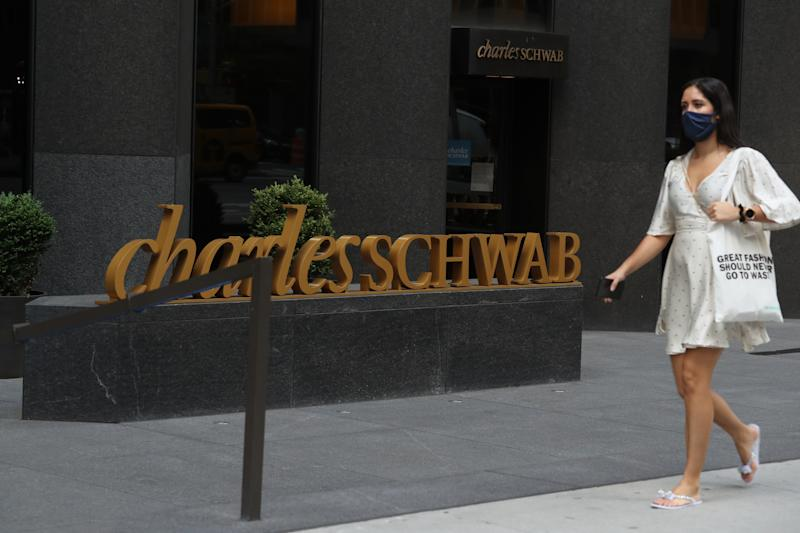 NEW YORK, NEW YORK - JULY 01: A person walks by the Charles Schwab logo in midtown as New York City moves into Phase 2 of re-opening following restrictions imposed to curb the coronavirus pandemic on July 1, 2020 in New York, New York. Phase 2 permits the re-opening of office jobs, real estate services, in-store retail services such as rentals, repairs and hair salons, and outdoor dining. (Photo by Rob Kim/Getty Images)