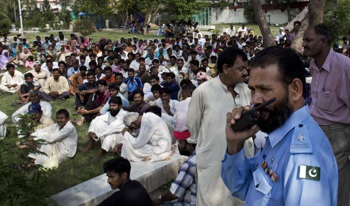 Hundreds of Christian families who fled their neighborhood where a girl was arrested on alleged blasphemy charges, fear backlashes from their Muslims neighbors if they had stayed, sit in a public park for protection in Islamabad, Pakistan, Tuesday, Aug. 28, 2102. Christians, who took refuge said that people burned their makeshift church to the ground late at night. (AP Photo/B.K. Bangash)
