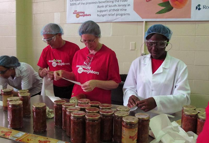 Campbell Soup Co. workers put labels on jars of  Just Peachy Salsa at the Campbell headquarters in Camden, N.J., on Wednesday, Aug. 1, 2012. Campbell and other firms are donating ingredients, materials and manufacturing for the salsa, which is being sold by the Food Bank of South Jersey. (AP Photo/Geoff Mulvihill)