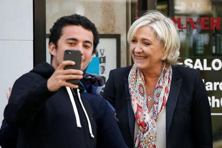 Marine Le Pen (R), French National Front (FN) political party leader and candidate for French 2017 presidential election, poses for a selfie as she leaves the haidresser in front of her campaign headquarters in Paris, France, April 24, 2017 the day after the first round of presidential elections where Le Pen ended in second place behind En Marche ! movement candidate. REUTERS/Charles Platiau