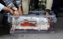 The flight data recorder from AirAsia QZ8501 is placed into a container upon its arrival at the airbase in Pangkalan Bun, Central Kalimantan January 12, 2015. REUTERS/Darren Whiteside