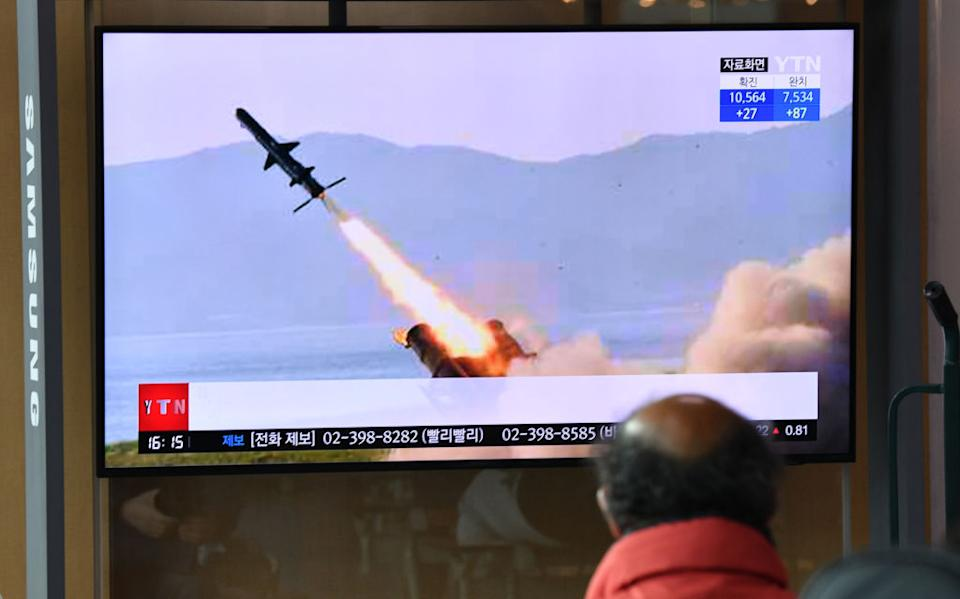 A man watches a television news broadcast showing file footage of a North Korean missile test.