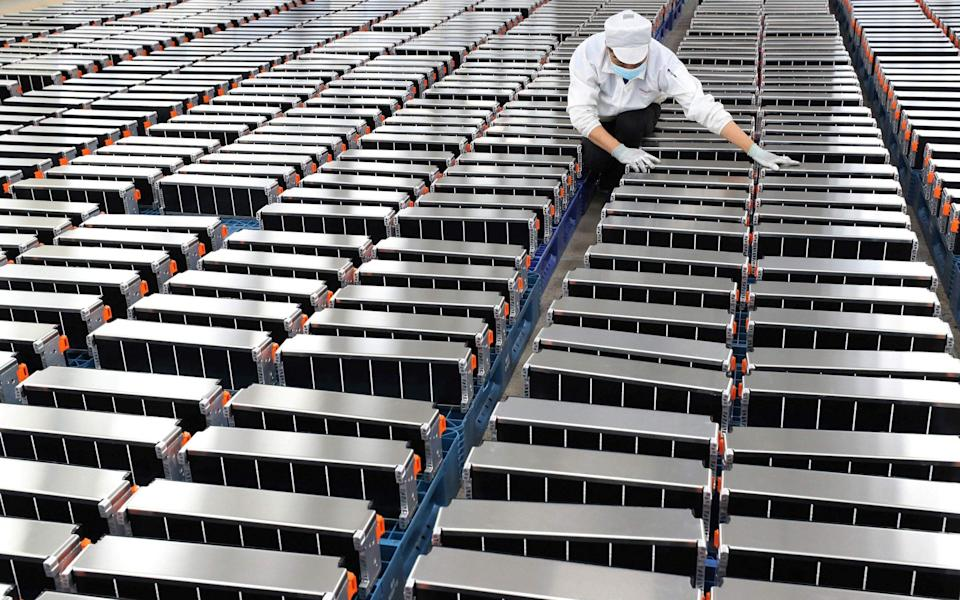 A worker with car batteries at a factory for Xinwangda Electric Vehicle Battery, which makes lithium batteries for electric cars - AFP/STR