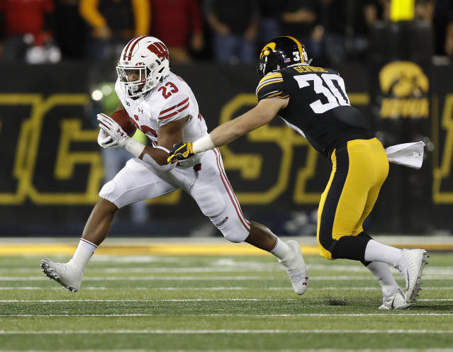 Wisconsin running back Jonathan Taylor, left, tries to get away from Iowa defensive back Jake Gervase during the first half of an NCAA college football game Saturday, Sept. 22, 2018, in Iowa City. (AP Photo/Matthew Putney)