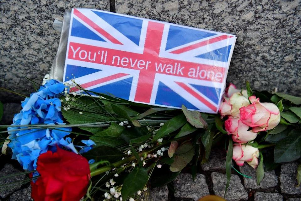 Flowers are left in a tribute to the victims of the London attack at the British embassy in Berlin (AFP Photo/John MACDOUGALL)