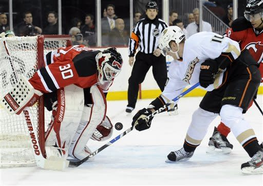 New Jersey Devils goaltender Martin Brodeur, left, makes a save on a shot by Anaheim Ducks' Corey Perry during the first period of an NHL hockey game Friday, Feb. 17, 2012, in Newark, N.J. (AP Photo/Bill Kostroun)