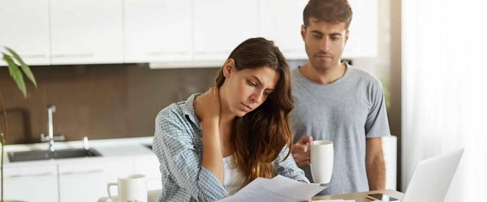 Stressed out couple sitting in kitchen, looking at bills and laptop.