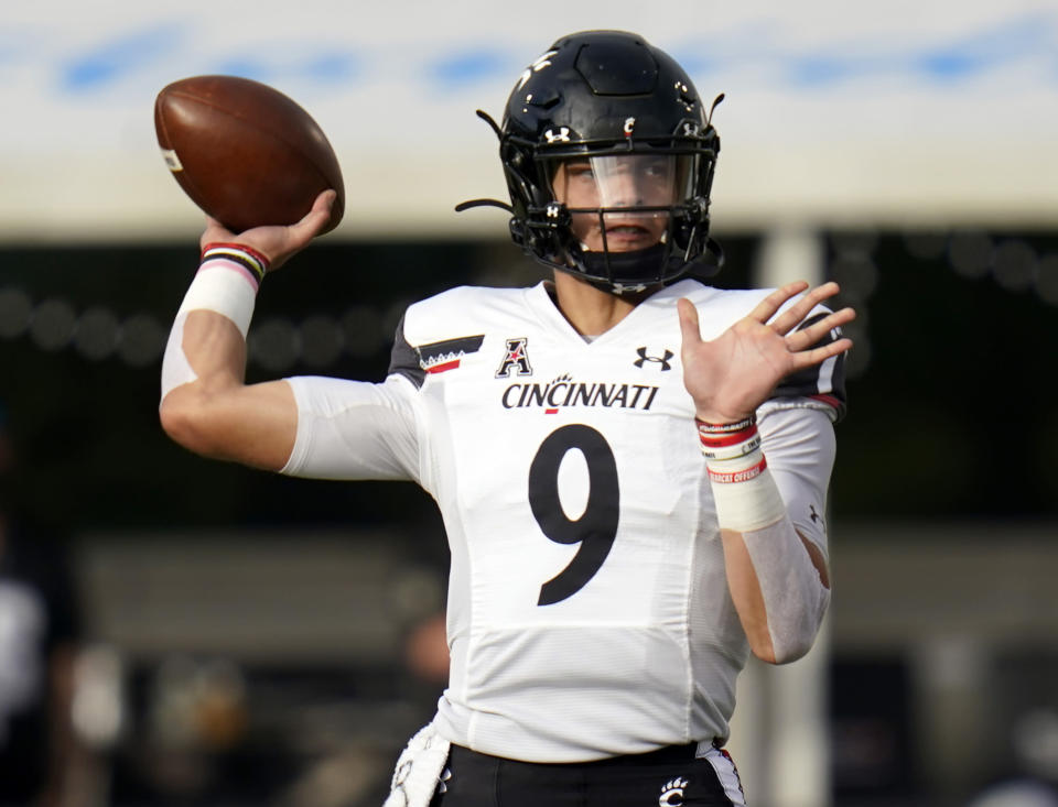 FILE - In this Nov. 21, 2020, file photo, Cincinnati quarterback Desmond Ridder looks for a receiver against Central Florida during the first half of an NCAA college football game in Orlando, Fla. In Ridder, the Bearcats have a guy that seems to get better with each game, so much so that NFL scouts have noticed. He ran for 12 TDs last season and completed two-thirds of his passes on a team better recognized for its defense. (AP Photo/John Raoux, File)