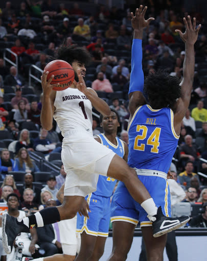 Arizona State's Remy Martin (1) passes around UCLA's Jalen Hill during the second half of an NCAA college basketball game in the quarterfinals of the Pac-12 men's tournament Thursday, March 14, 2019, in Las Vegas. (AP Photo/John Locher)