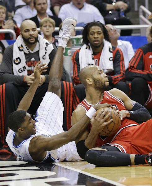 Chicago Bulls' Taj Gibson, right, and Orlando Magic's E'Twaun Moore, left, scramble for a loose ball in front of the Chicago bench during the first half of an NBA basketball game in Orlando, Fla., Wednesday, Jan. 15, 2014. (AP Photo/John Raoux)