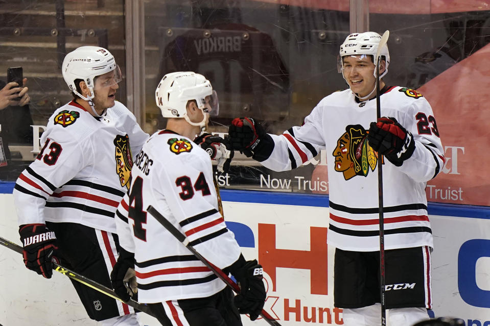 Chicago Blackhawks center Philipp Kurashev (23) is congratulated by teammates Mattias Janmark (13) and Carl Soderberg (34) after he scored a goal during the second period of an NHL hockey game against the Florida Panthers, Monday, March 15, 2021, in Sunrise, Fla. (AP Photo/Wilfredo Lee)