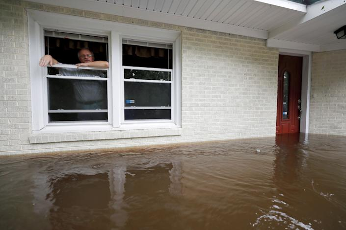 Obrad Gavrilovic peers out the window of his flooded home while considering whether to leave with his wife and pets, as waters rise in Bolivia, North Carolina.