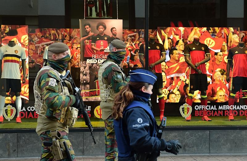 Soldiers and police patrol past closed shops as the Belgian capital remains on the highest possible alert level, in Brussels on November 23, 2015