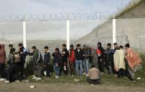"""FILE - In this Oct. 27, 2016 file photo, Migrants queue for busses to leave the makeshift migrant camp known as """"the jungle"""" near Calais, northern France. Refugees who stayed at such camps during a 2015 wave of mass migration to Europe have lessons to share with the more than 124,000 people airlifted out of Afghanistan during the U.S.-led evacuation in 2021. (AP Photo/Matt Dunham, File)"""