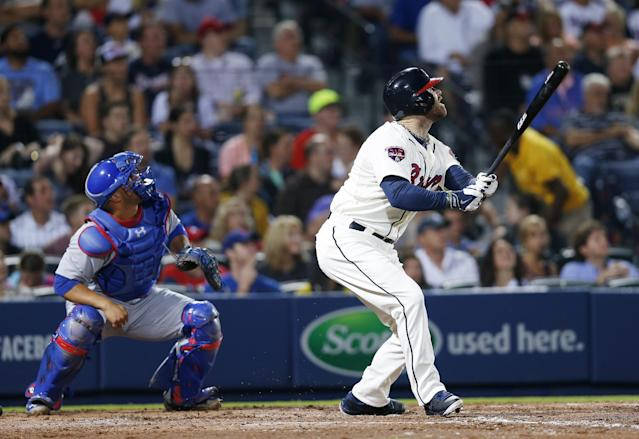 Atlanta Braves pitch hitter Ryan Doumit (4) follows through with an RBI double as Chicago Cubs catcher Welington Castillo (5) looks on in the seventh inning of a baseball game Saturday, May 10, 2014 in Atlanta. (AP Photo/John Bazemore)
