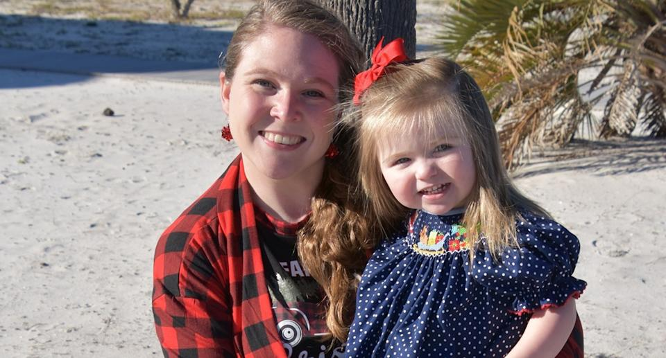 Haley Richardson wearing a red checked shirt holding her daughter Katie smiling at the camera.