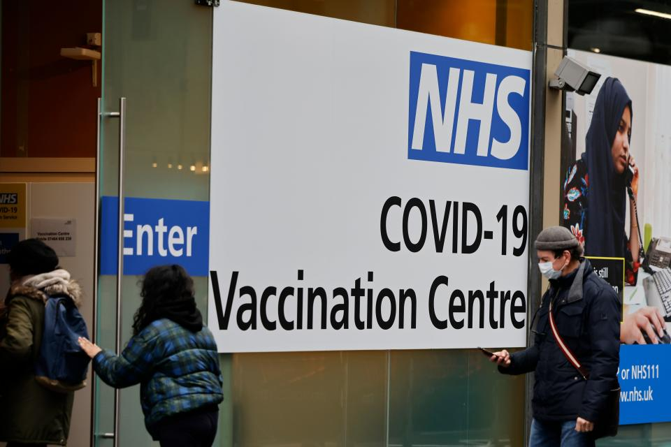 People queue to enter the NHS Covid-19 vaccination centre in Westfield Stratford City shopping centre in east London on February 15, 2021 as Britain's largest ever vaccination programme continues. - Prime Minister Boris Johnson called Britain hitting a target of inoculating 15 million of the most vulnerable people with a first coronavirus jab