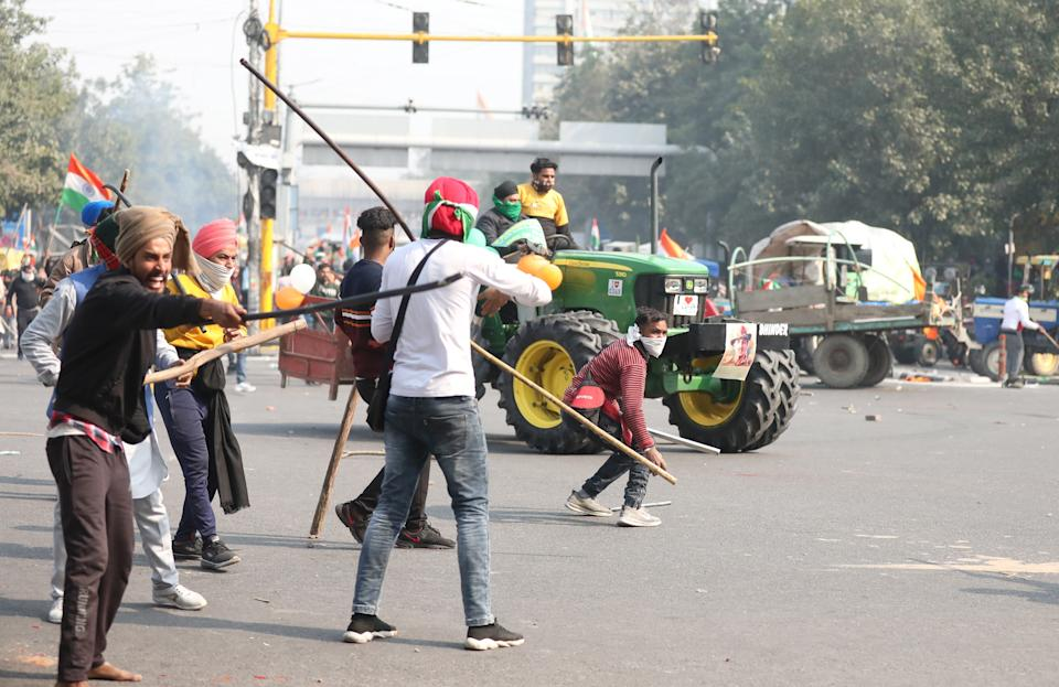 Farmers hold sticks as they confront police officers in Delhi (EPA)