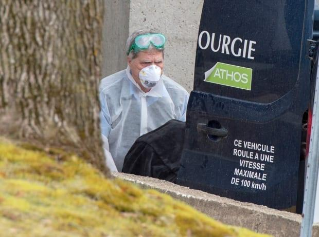 A funeral home worker removes a body from the CHSLD Sainte-Dorothée in Laval in April 2020. More than 100 residents died of COVID-19 at the home. (Ryan Remiorz/The Canadian Press - image credit)