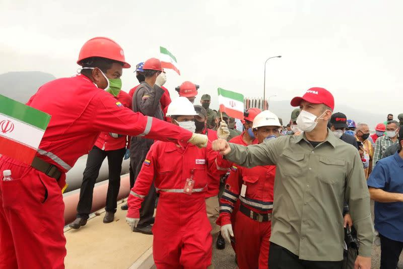 """FILE PHOTO: A worker of the state-oil company Pdvsa greets Venezuela's Oil Minister Tarek El Aissami during the arrival of the Iranian tanker ship """"Fortune"""" at El Palito refinery in Puerto Cabello"""