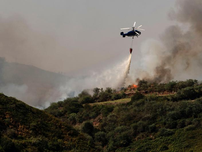 A helicopter operates over a wildfire in Canary Islands, Spain, Monday, Aug. 19, 2019.