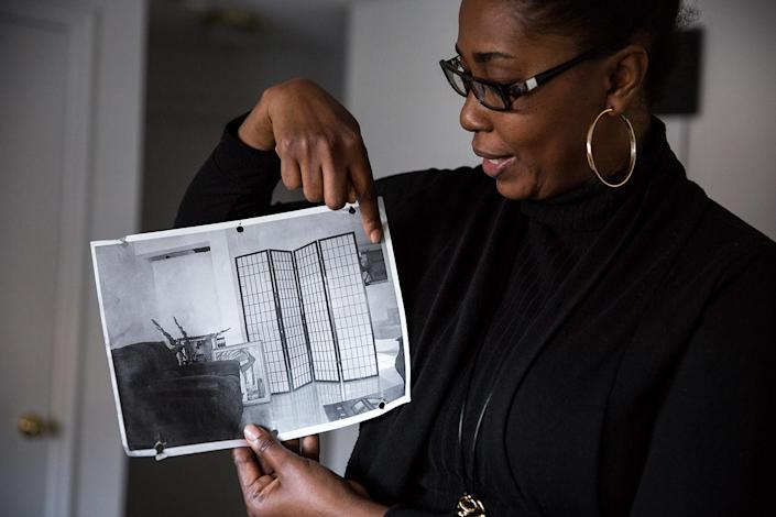 Mona Pompilus displays a photo of the living room in her home in Haiti that was badly damaged by the 2010 earthquake. (Photo: Kayana Szymczak for Yahoo News)