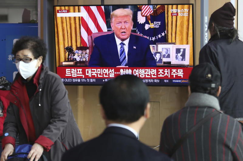 "People watch a TV screen showing a live broadcast of U.S. President Donald Trump's speech at the Seoul Railway Station in Seoul, South Korea, Thursday, March 12, 2020. Trump announced he is cutting off travel from Europe to the U.S. and moving to ease the economic cost of a viral pandemic that is roiling global financial markets and disrupting the daily lives of Americans. The Korean letters read: ""Trump national speech."" (AP Photo/Ahn Young-joon)"
