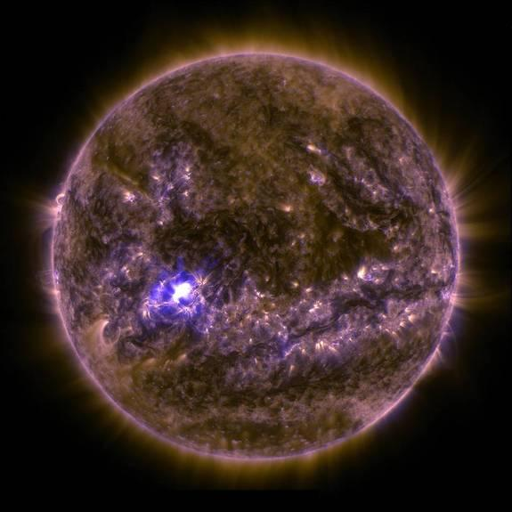 NASA's Solar Dynamics Observatory captured an image of an X2.2 solar flare on March 11, 2015, seen as a bright flash of light on the left side of the sun. Earth is shown for scale.