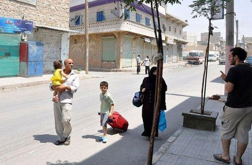 A Syrian family walks past closed shops as they flee the Shaar neighborhood of the restive city of Aleppo
