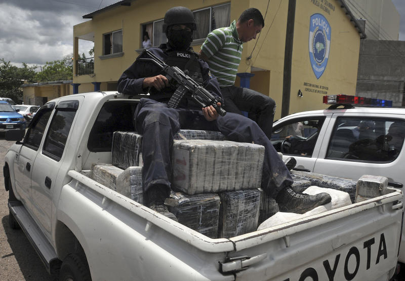 A Honduras national policeman sits on packages of cocaine that were brought to Tegucigalpa, Honduras, Tuesday July 3, 2012. The cocaine was seized from a small airplane that crashed after it was being chased by military planes and helicopters of the Honduras army near the town of Los Lirios, about 217 miles (350 km) east of Tegucigalpa. One of the pilots died and the other was injured. About 1322 lbs. (600 kg.) of cocaine were seized. (AP Photo/Fernando Antonio)