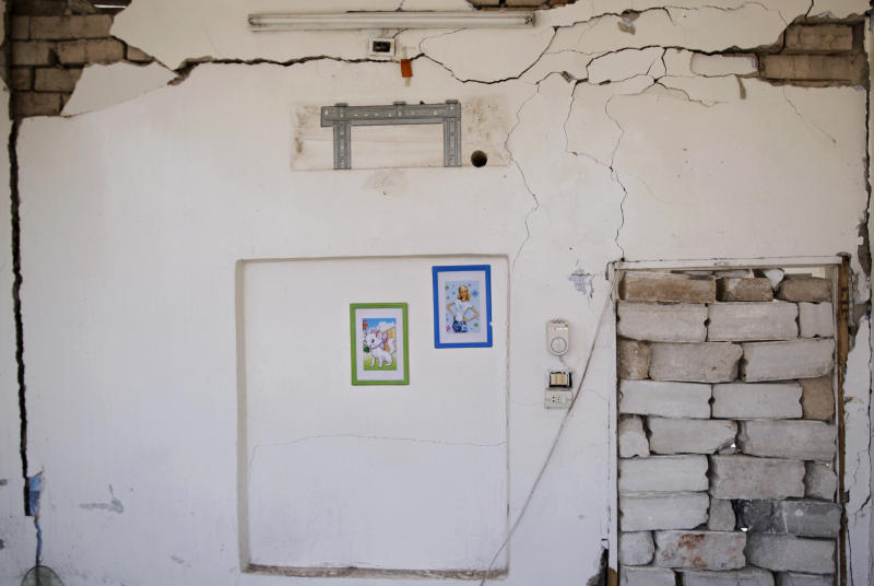 In this Wednesday, Aug. 29, 2012 photo, two photos hang on a damaged wall in the room that belonged to a Syrian girl, Sara Makour, 11, who lost her life along with her brother, Youssuf, a year and a half old, in a Syrian government airstrike on August 15, 2012, that killed more than 40 people and destroyed more than a dozen homes in Azaz, on the outskirts of Aleppo, Syria. Over the past week, survivors and relatives have returned daily to collect from the rubble what can be salvaged as they also relive the day of the airstrike. (AP Photo/Muhammed Muheisen)