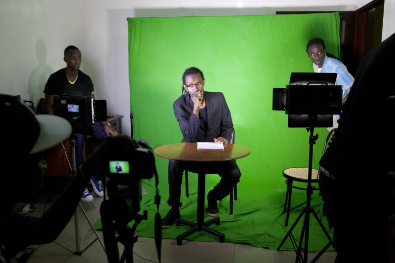 In this photo taken Tuesday, Sept. 10, 2013, rapper Makhtar 'Xuman' Fall lays down verse about the week's news, during a taping of the 'Journal Rappe' in Dakar, Senegal. In the span of a program just five minutes long, Fall and his co-host Cheikh 'Keyti' Sene tackle, in rhyming verse, everything from the Middle East to local woes like the flooding that disproportionately hits poor suburbs of Senegal's capital. The news and commentary show, rapped in French and Wolof, went viral on YouTube earlier this year and now airs twice a week on Senegalese television. (AP Photo/Jane Hahn)